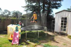 Jumping on the trampoline with a sprinkler underneath to beat the heat.  Daddy models.